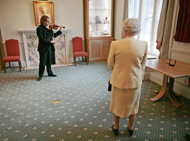 Her Majesty, Queen Elizabeth II, watches a performance by Giovanni Guzzo on a Stradivarius violin at the Royal Academy of Music in London.