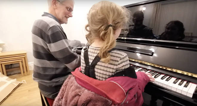 The little girl joins her grandad at the piano for a duet in the festive advert