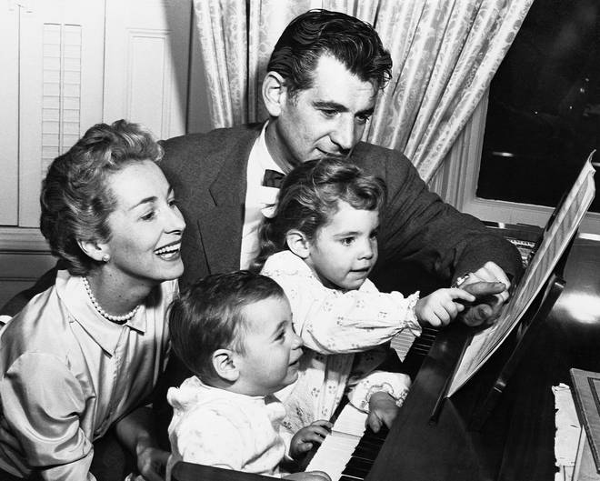 Leonard Bernstein plays piano with his sons, as wife Felicia looks on.