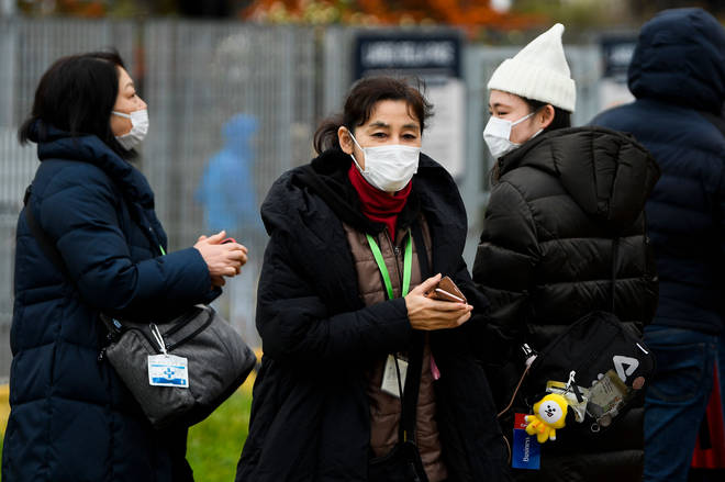 Passengers wearing respiratory masks exit the port of Civitavecchia, north of Rome, early on January 31, 2020