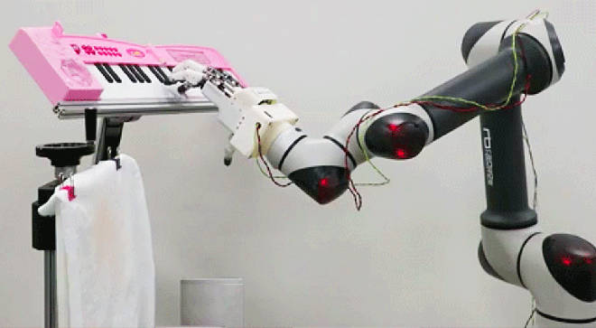 Robotic hand plays notes on a keyboard