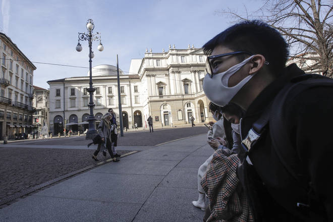 Locals wearing masks sit in front of La Scala opera house in Milan, Italy