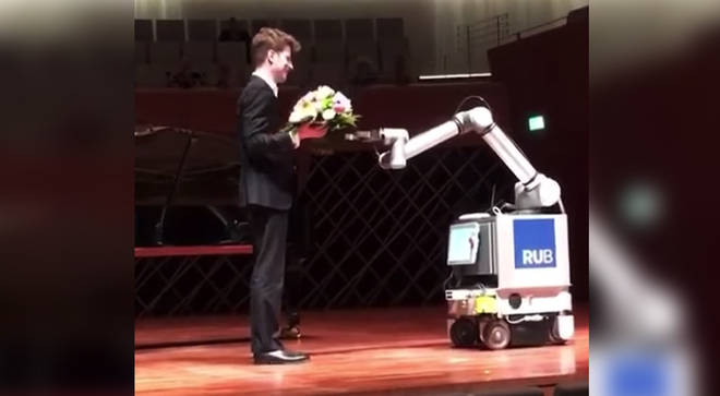 Pianist receives flowers from a robot after his performance