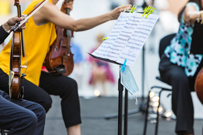 A face mask hangs from the music stand of a musician playing at an open-air concert in Madrid