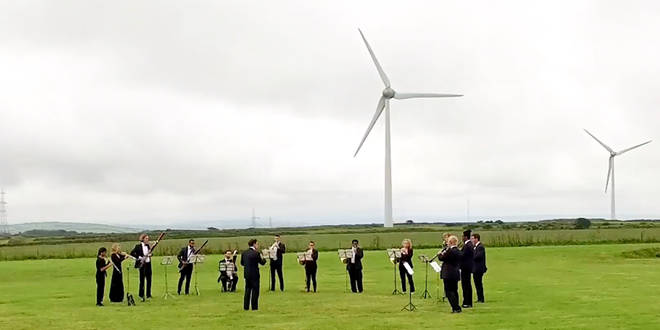 Orchestra for the Earth perform under wind turbines to mark this year's Earth Overshoot Day