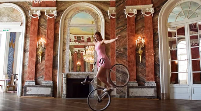 Ballerina performs dance routine on a bike