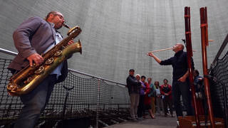 Baritone sax and overtone flute improvise duet in giant cooling tower
