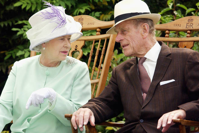 2002: Queen Elizabeth II and the Duke of Edinburgh chat while watching a musical performance in the Abbey Gardens during her Golden Jubilee visit to Suffolk