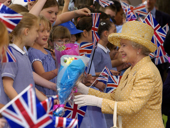 The Queen is given flowers from schoolgirls during her Golden Jubilee visit to West London
