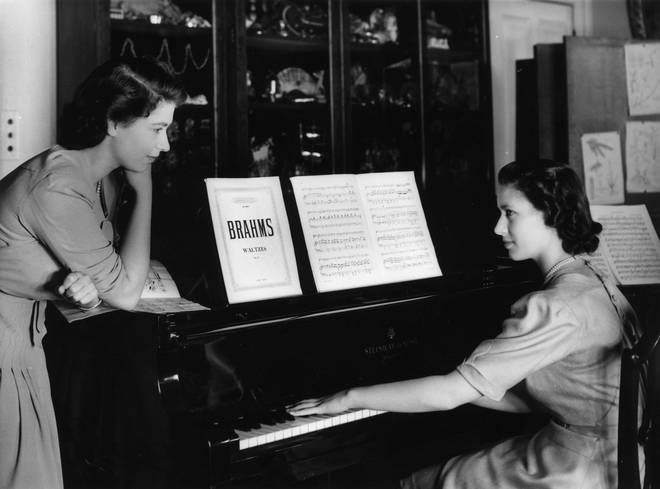 Princess Elizabeth watches her sister, Princess Margaret play a Brahms Waltz on the piano in the school room at Buckingham Palace.