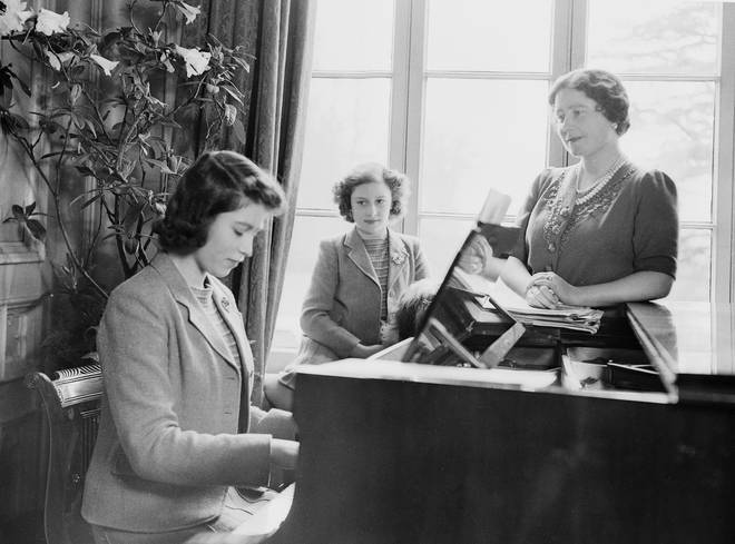 Princess Elizabeth plays the piano as Queen Elizabeth and Princess Margaret look on at the Royal Lodge in Windsor Castle