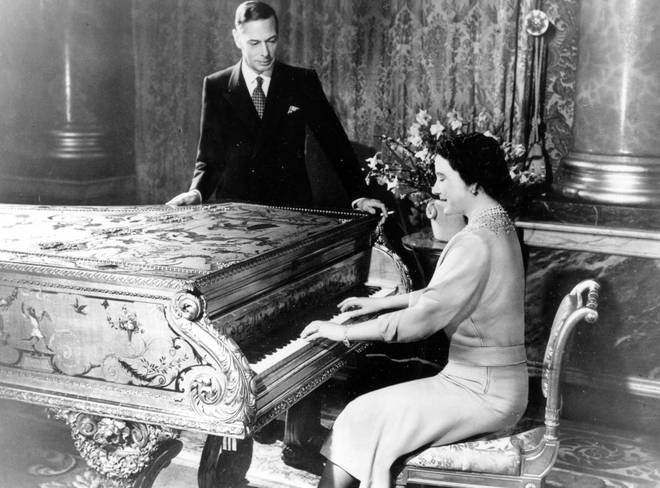 George VI watches as Queen Elizabeth (The Queen Mother) plays piano
