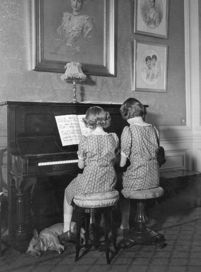 Princess Elizabeth and Princess Margaret seated together at the piano at Windsor Castle, 1940.