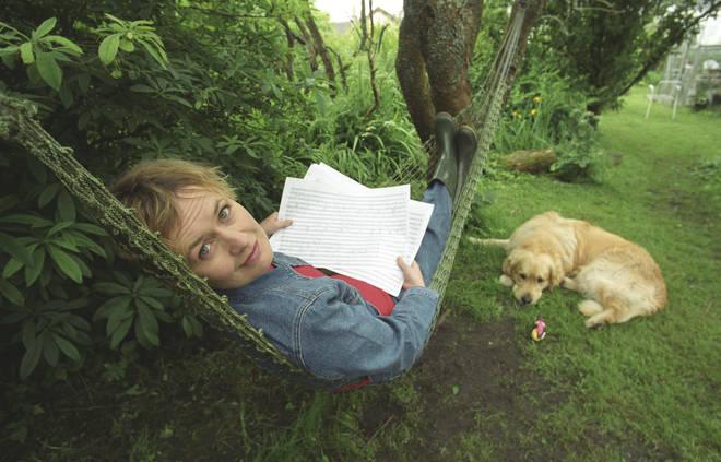 Sally Beamish on a hammock, with a dog.