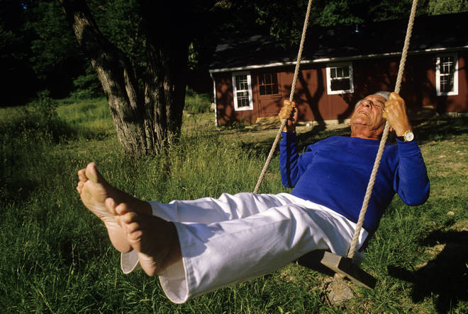 Composer Leonard Bernstein swings outside of his Fairfield, Connecticut home (1986)