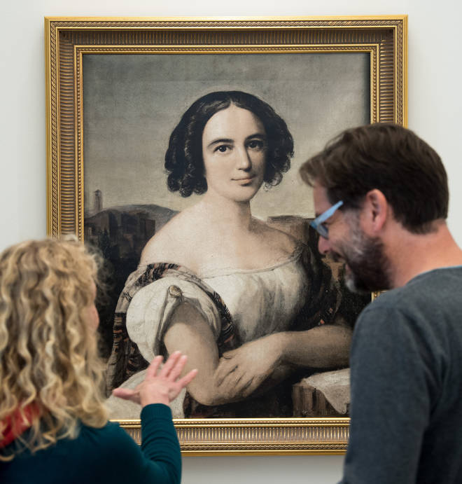 Visitors looking at a reproduction of an oil painting depicting Fanny Hensel