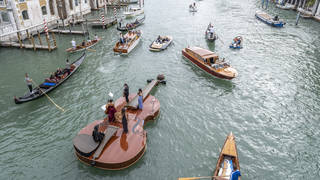 Violin-shaped boat parades near the Accademia Bridge in Venice, Italy.