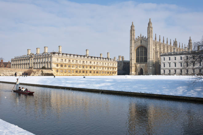 Punting along river Cam in winter snow with Kings College Chapel to the rear Cambridge, England