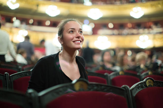 Portrait of excited young woman in auditorium of theatre
