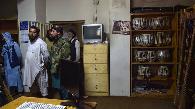 Taliban fighters standing in a room where instruments are kept at the Afghanistan National Institute of Music in Kabul