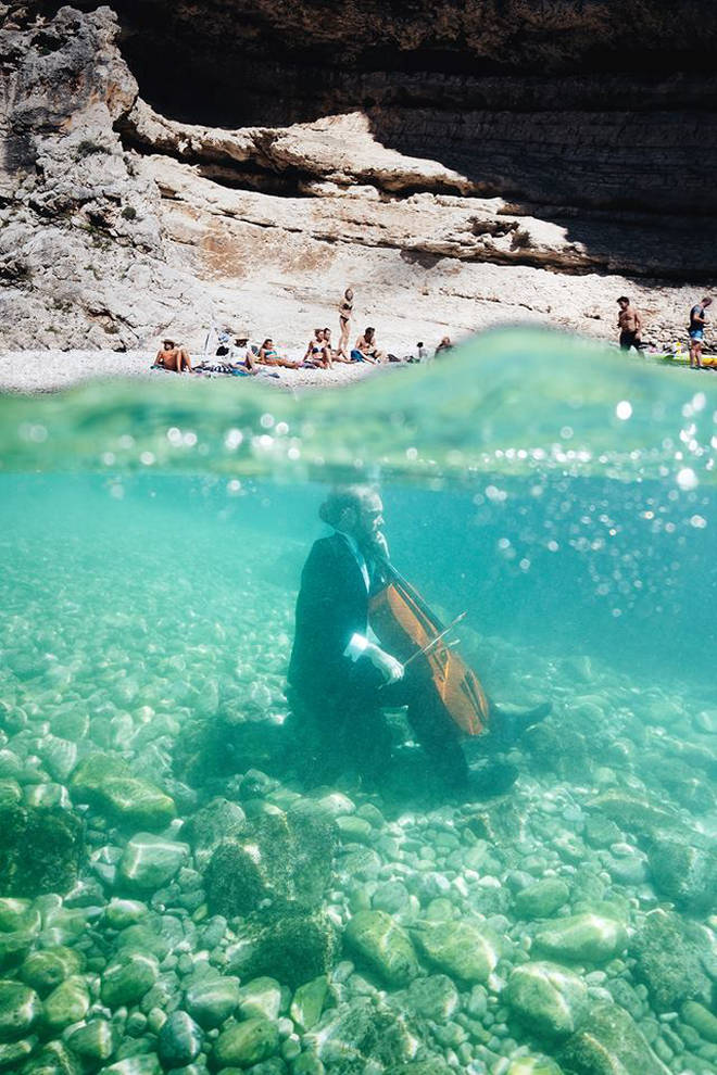 Møldrup took the cello underwater as holiday goers watched from the beach