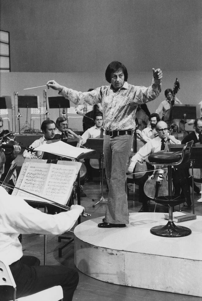Conductor André Previn leading an orchestra in 1974