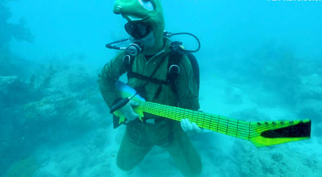 Underwater guitar player dressed as a turtle