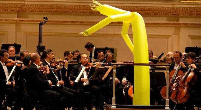 Inflatable man conducts an orchestra
