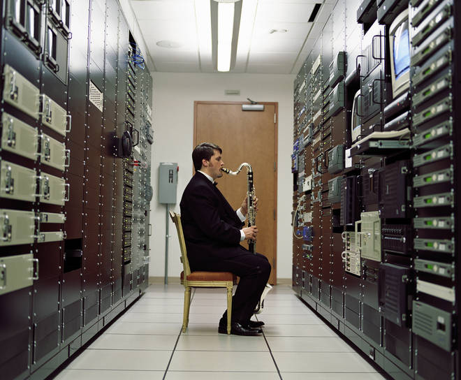 Man playing bass clarinet in a server room